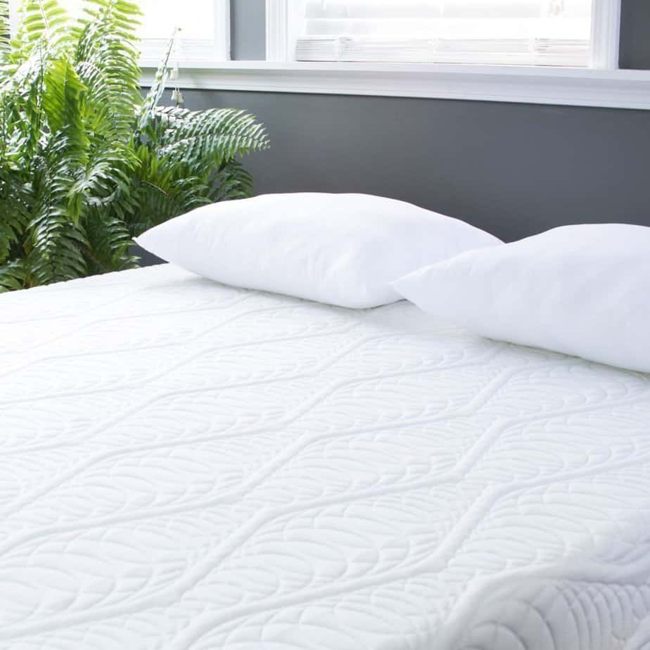 the eLuxury Supply Mattress with pillows laid on a wooden bed