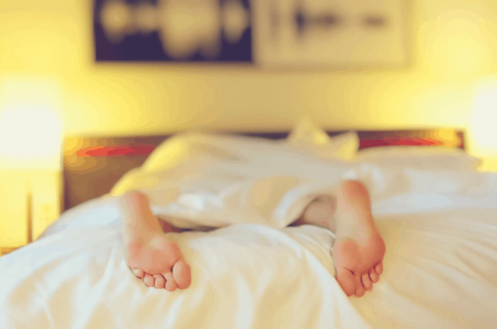 woman lying on a bed with crisp white sheets in a blurred background