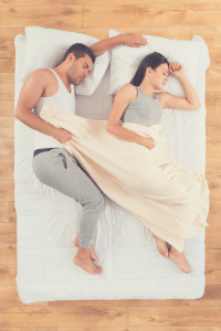 couple sleeping on a mattress on the floor