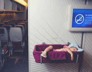 2-year old sleeping soundly in a toddler bed while on a flight