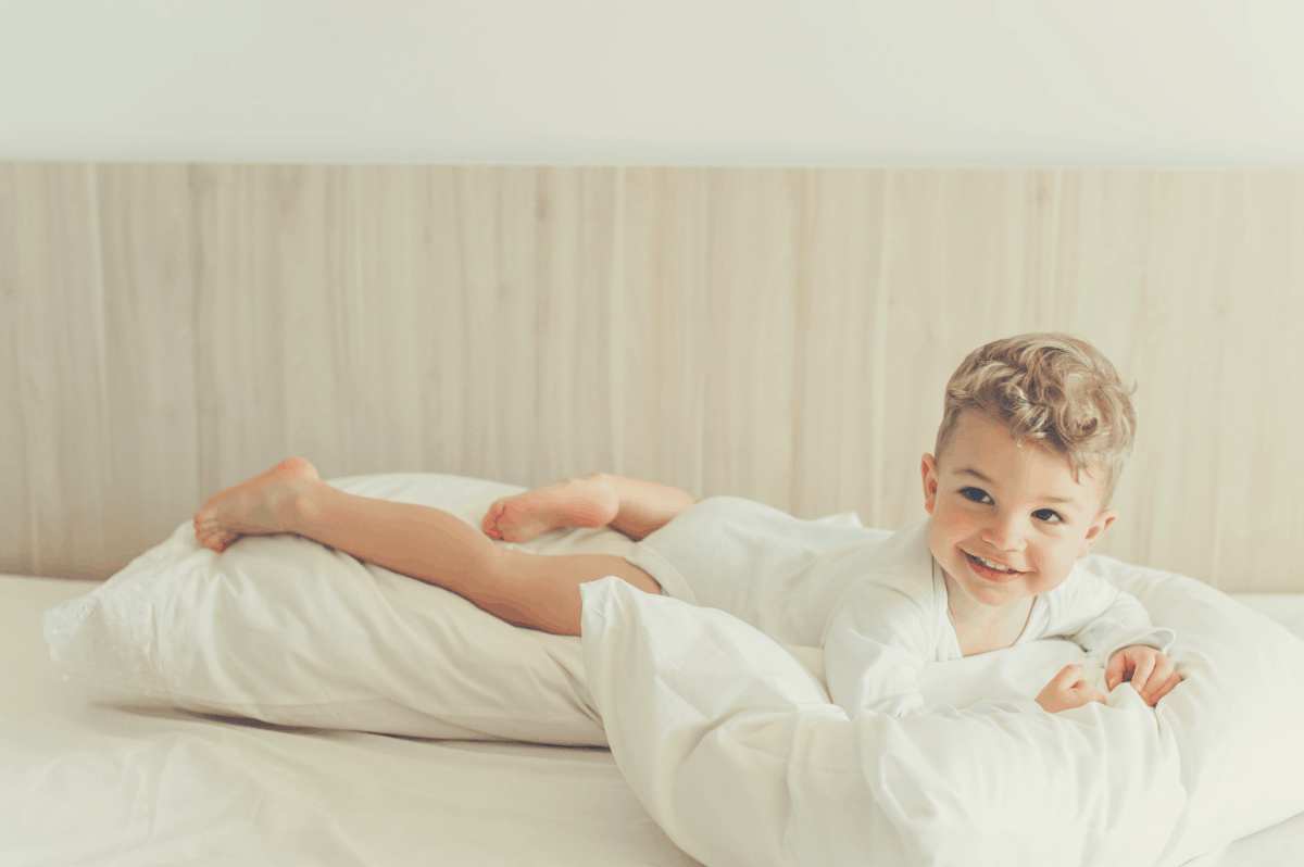 smiling toddler boy playing with pillows in bed