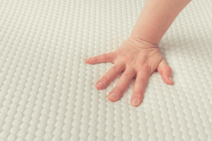 woman feeling the firmness of a mattress Topper