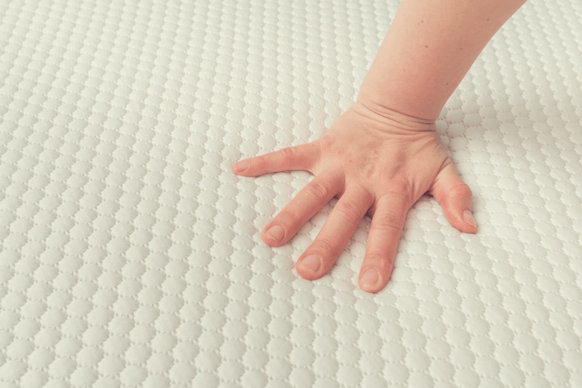woman feeling the firmness of a mattress Topper
