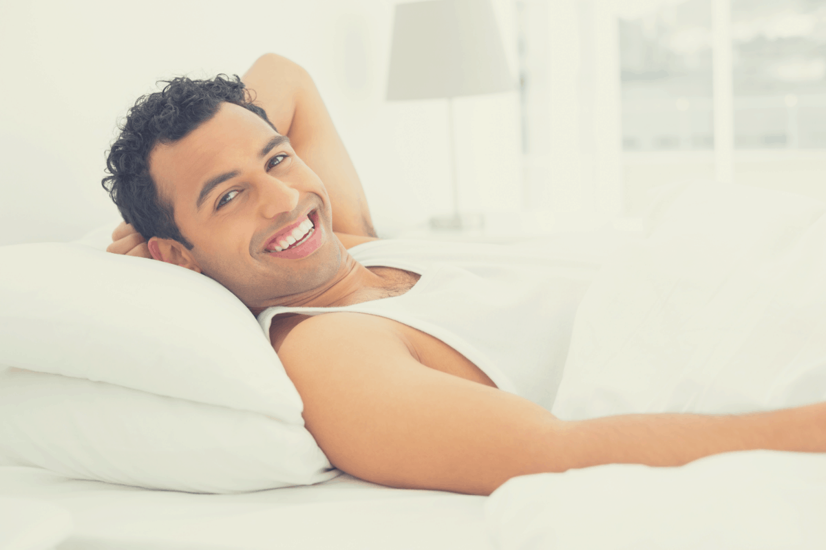 man smiling while lying on a pillow in bed