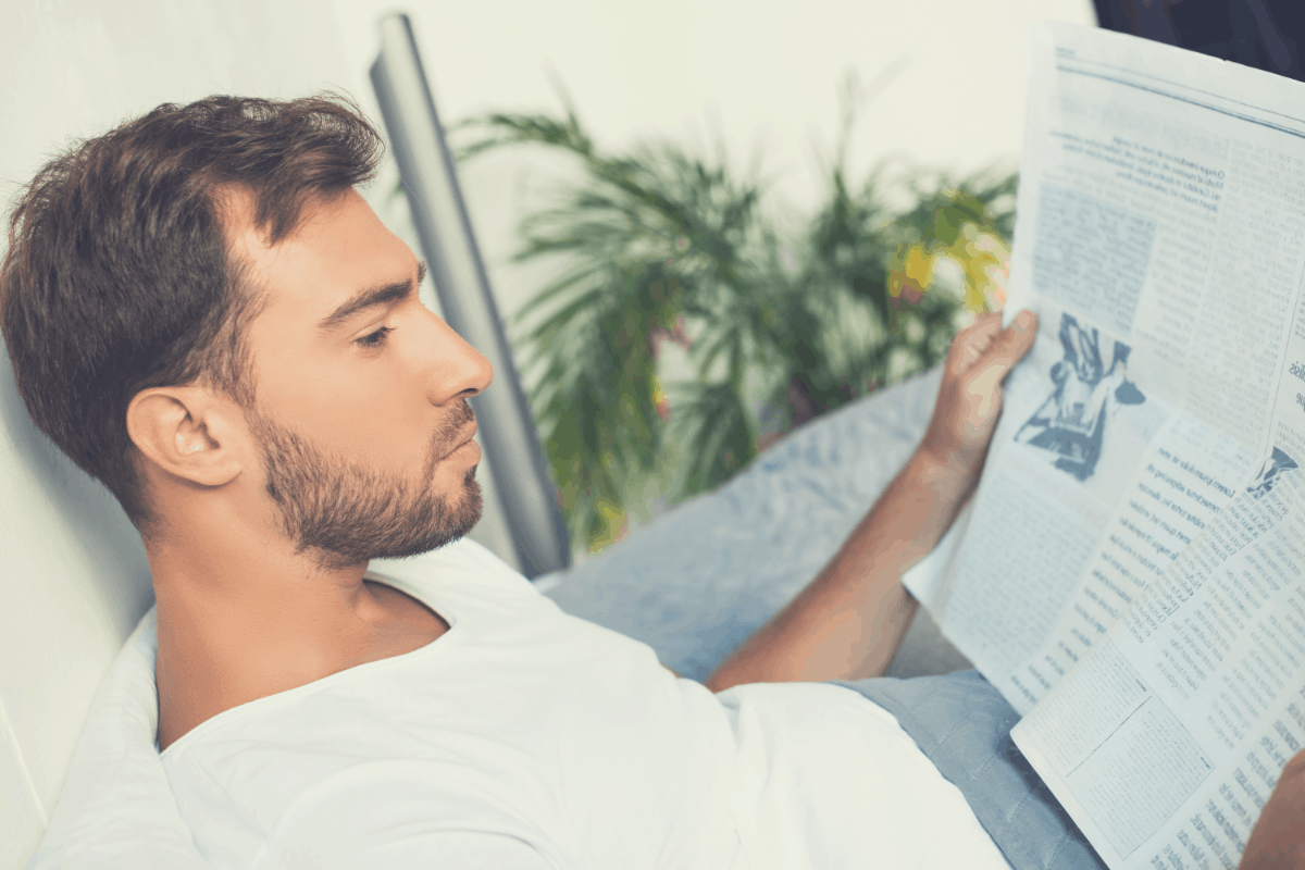 man reading a newspaper in bed with his back resting on a pillow