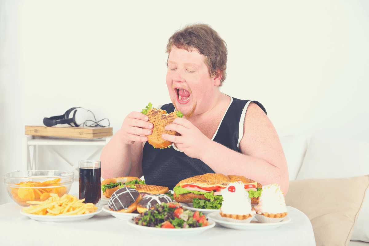overweight man eating several plates of food