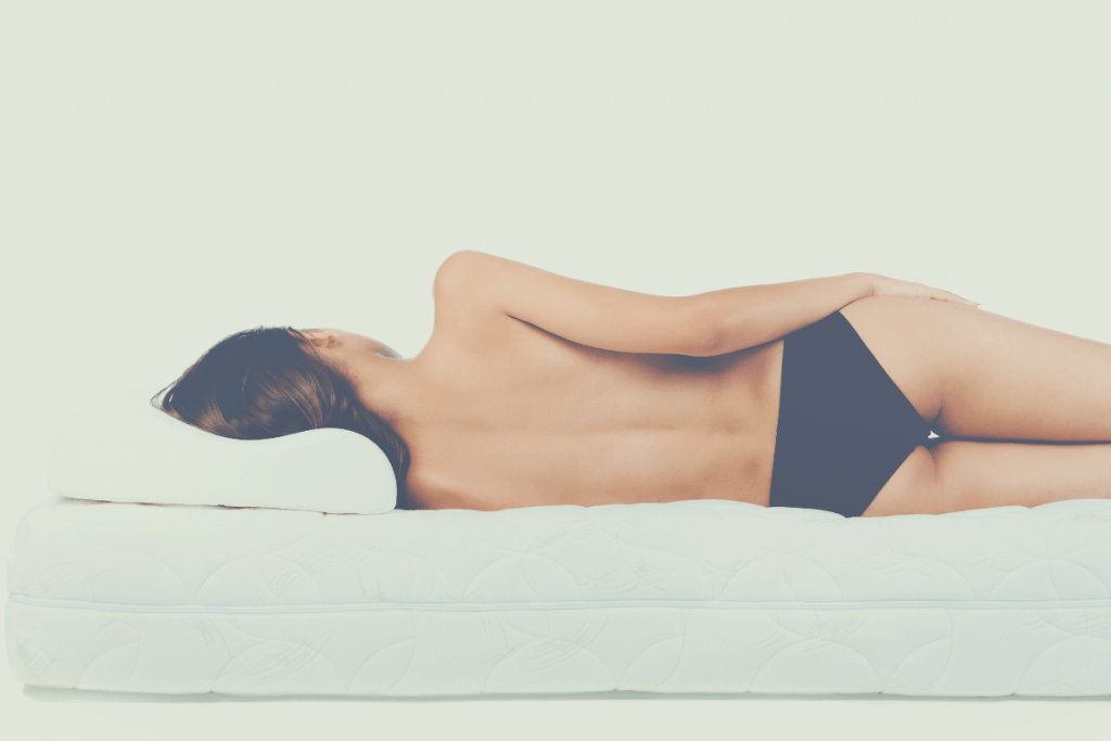topless woman lying on a mattress without sheets