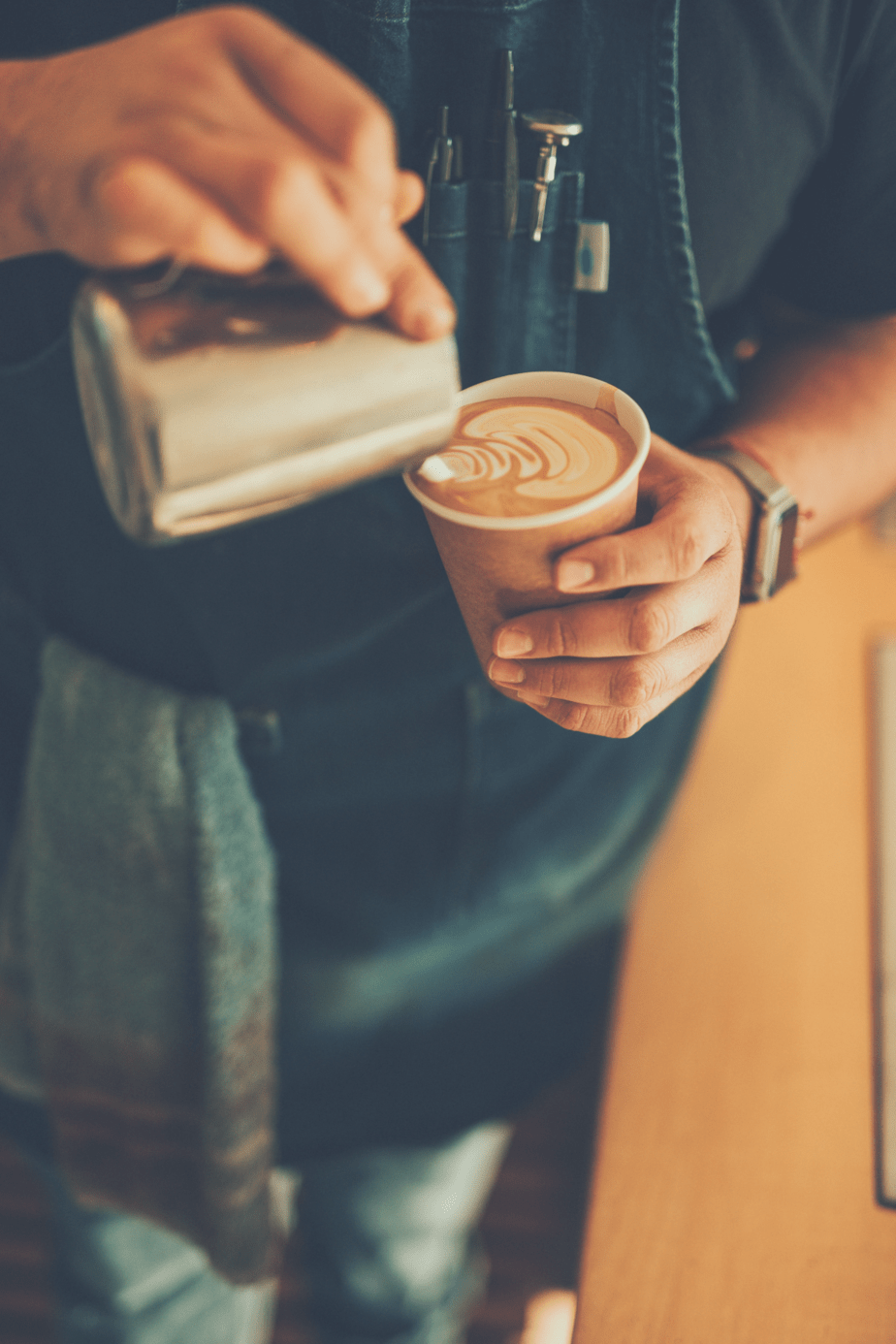 barista pouring a cup of coffee