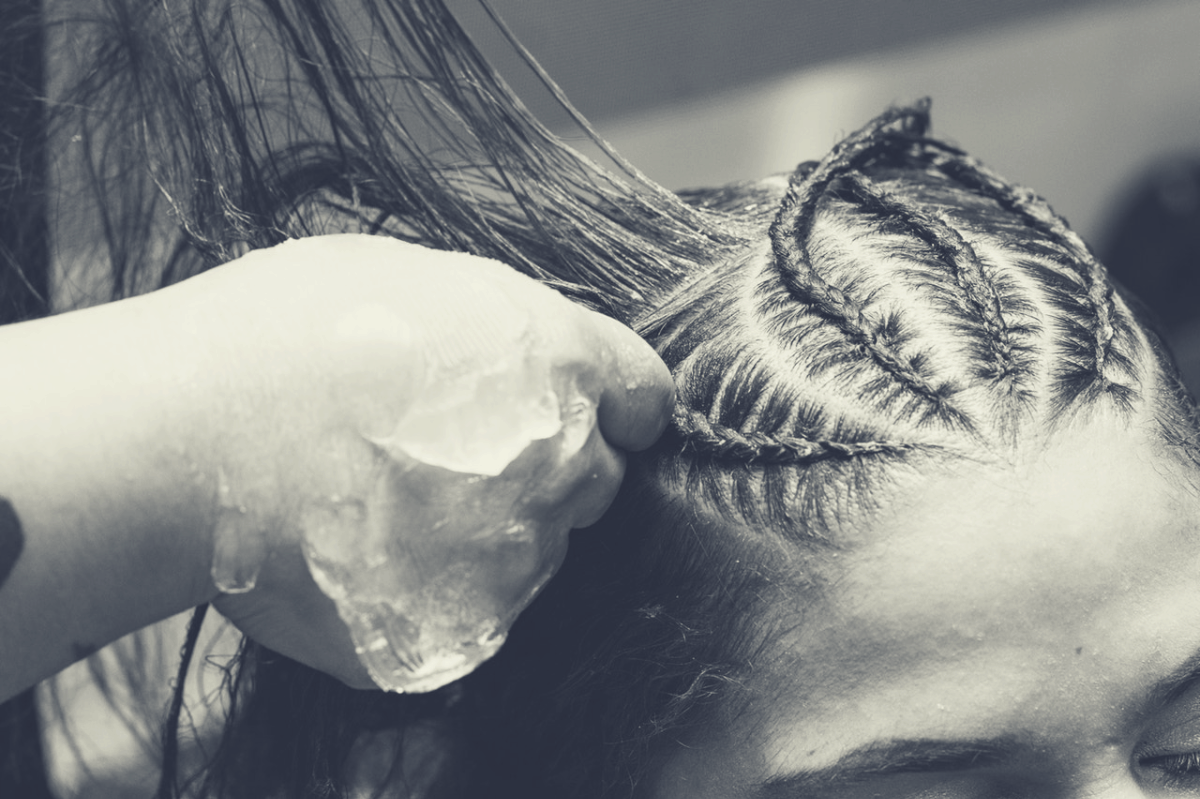 woman carefully being braided