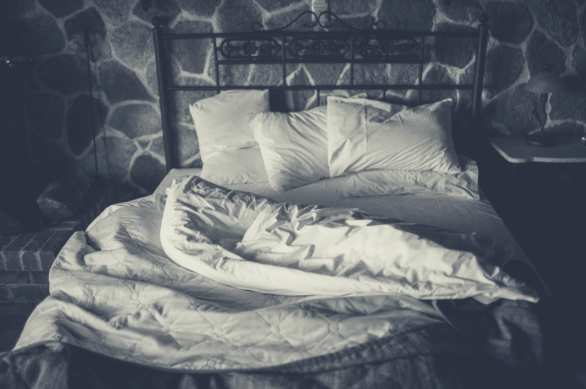 black and white image of duvets on a metal bed