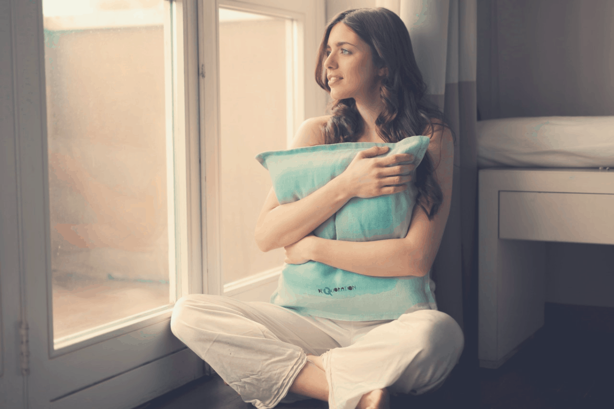 lady at her window hugging a body pillow