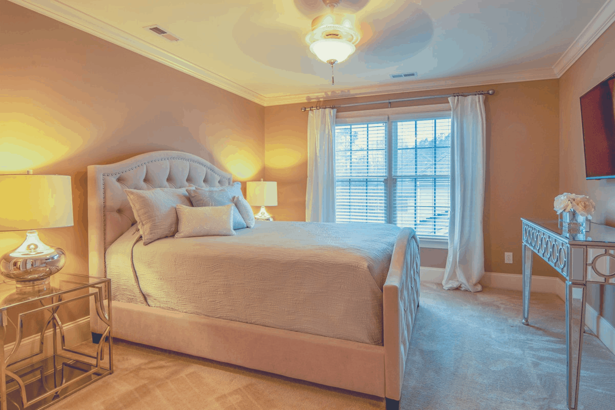 bedroom with comfy platform bed laid with sheets and 3 pillows