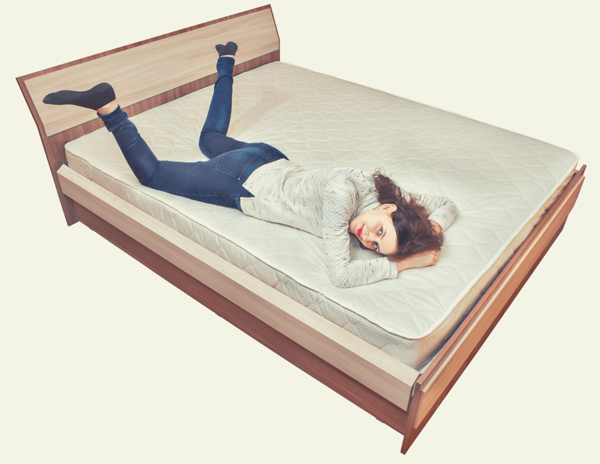 caucasian woman lying down on an innerspring mattress on laid on a wooden bed