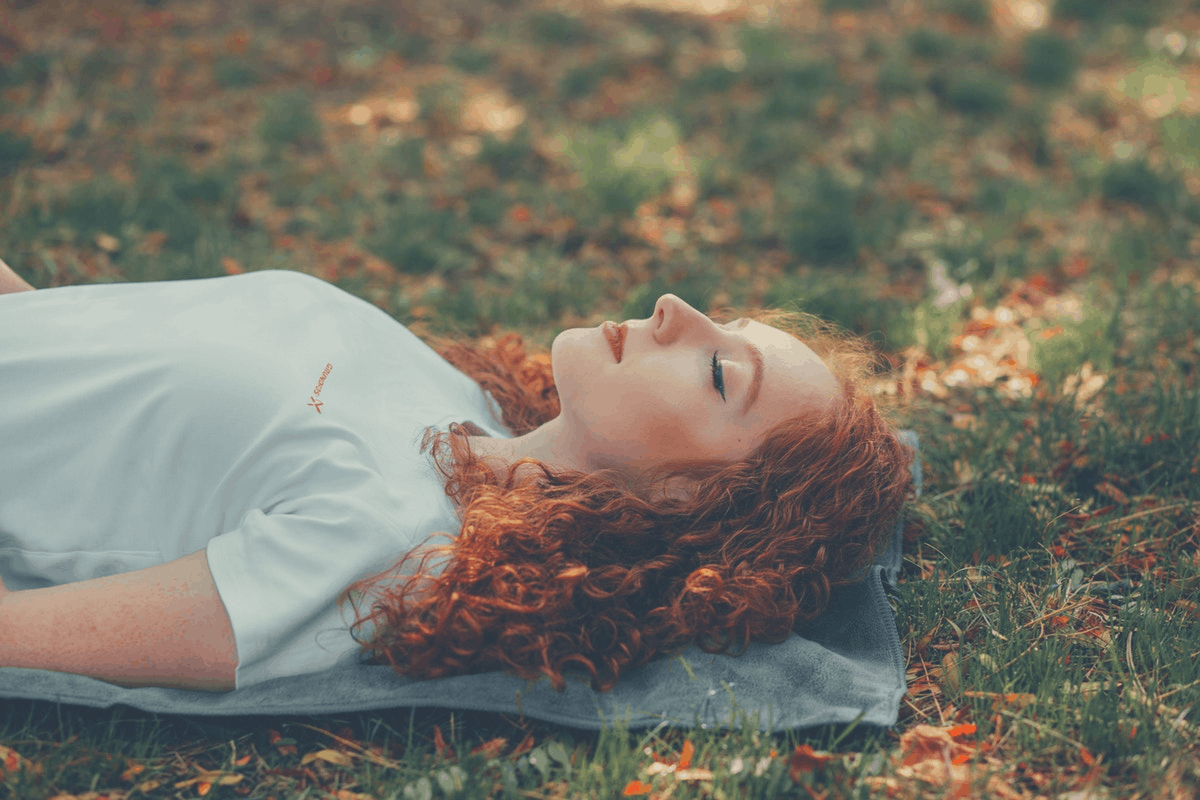 woman napping on grass outdoors