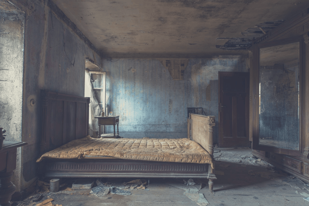 old mattress on a wooden bed in an abandoned bedroom