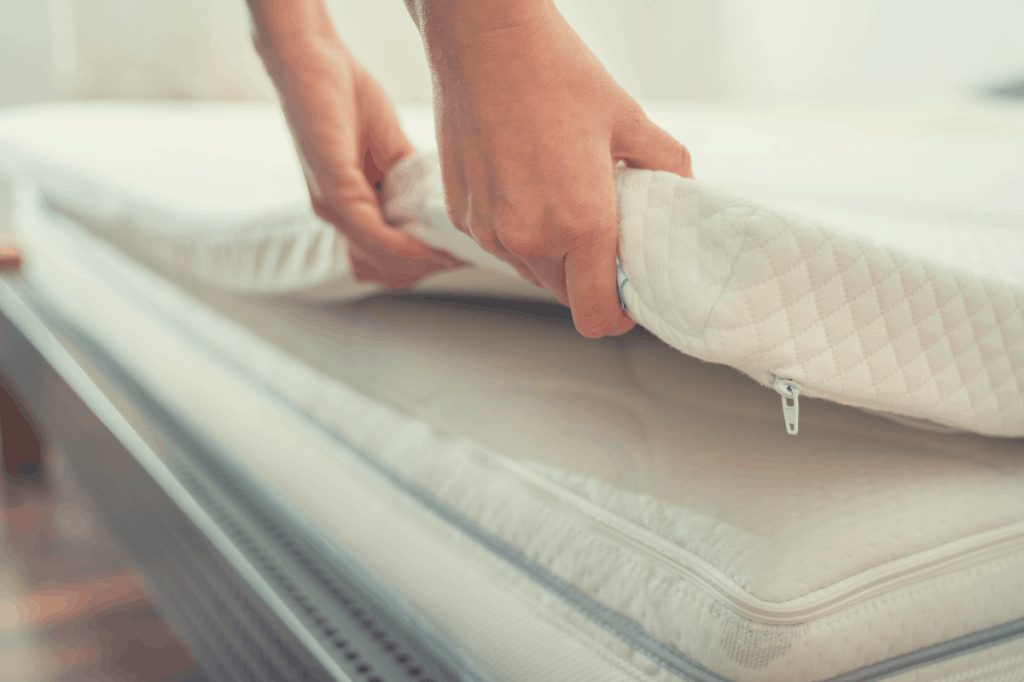 mattress topper being laid on a regular mattress