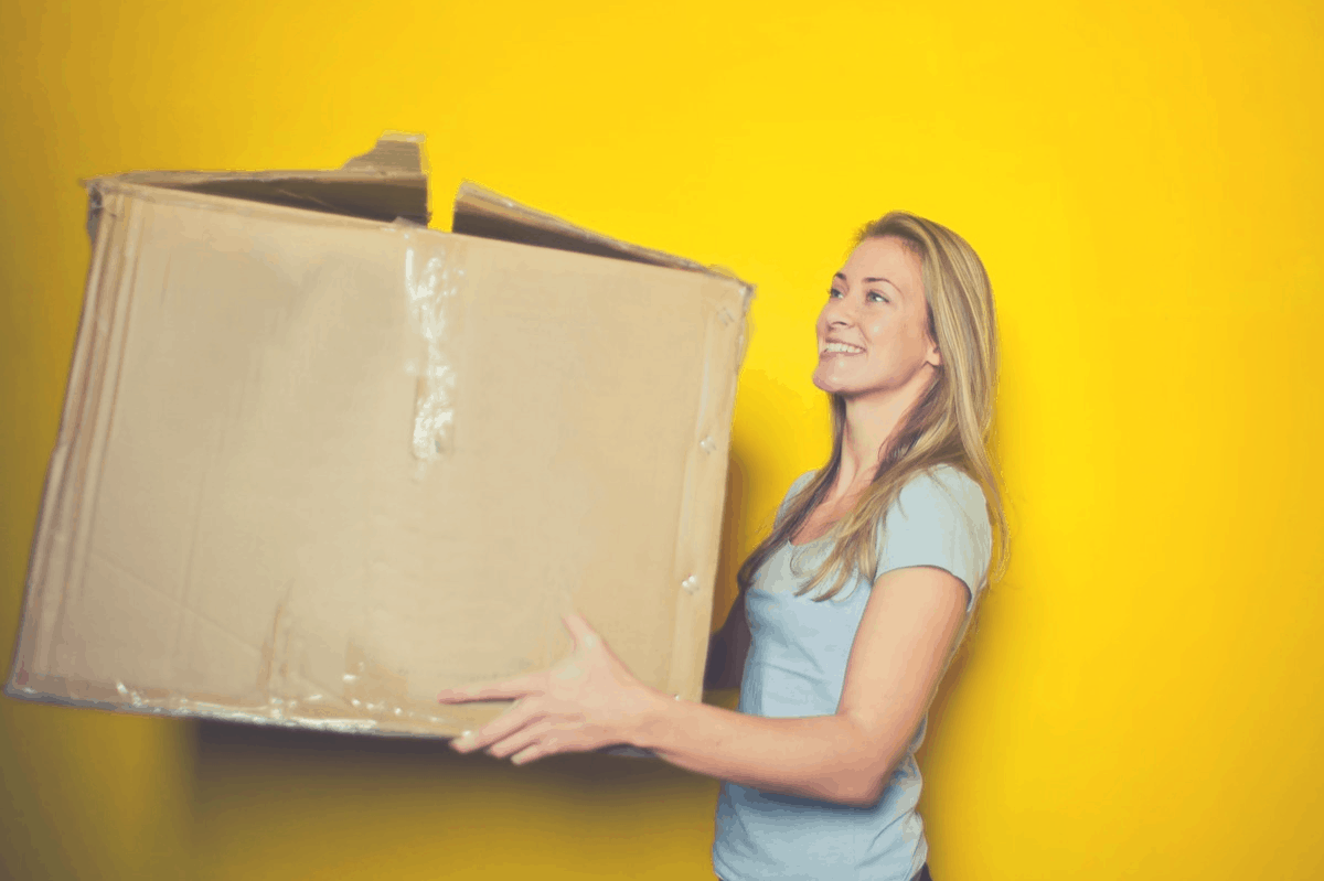 blonde holding a big brown packaging box