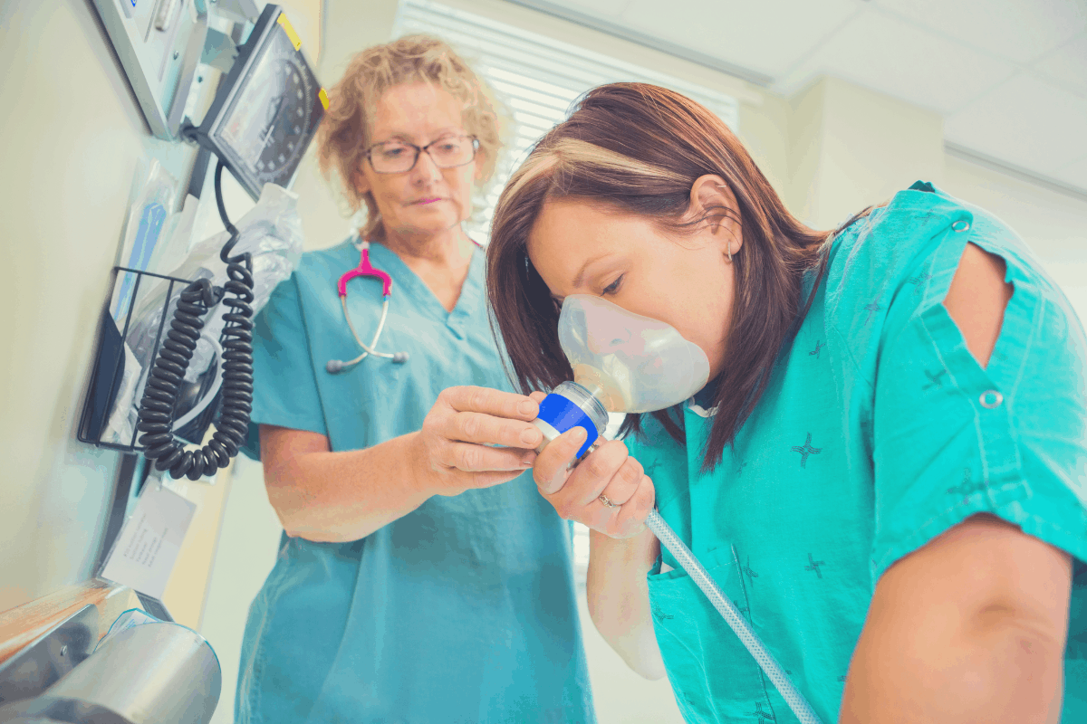woman inhaling laughing gas under supervision by a doctor