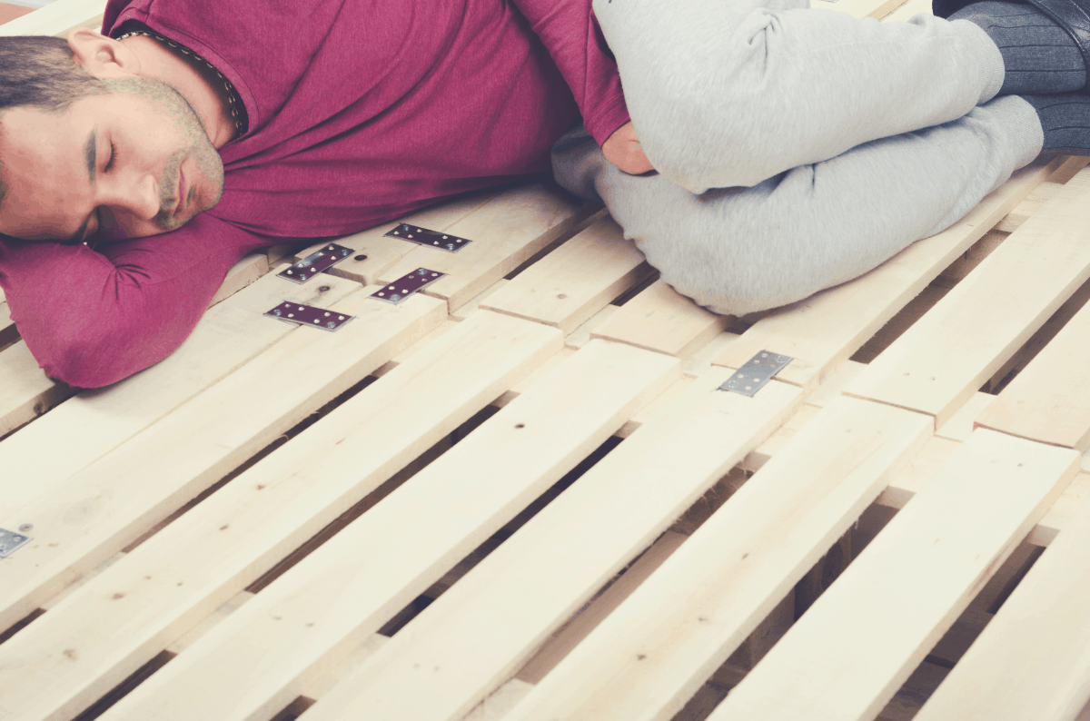 man lying down on wooden bed slats