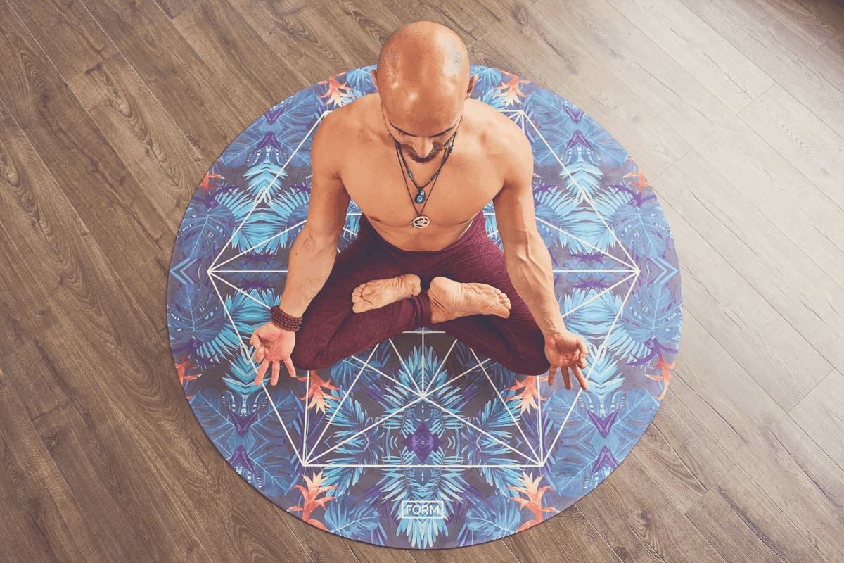 bare-chested man meditating on a hardwood floor