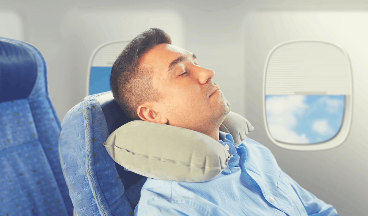 man resting his head on a travel pillow