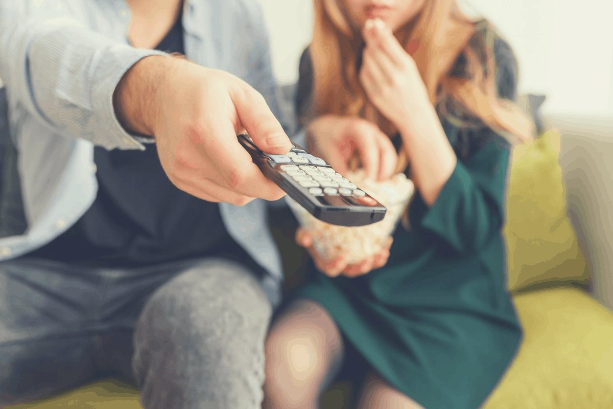 couple sitting in the couch with one turning on the TV