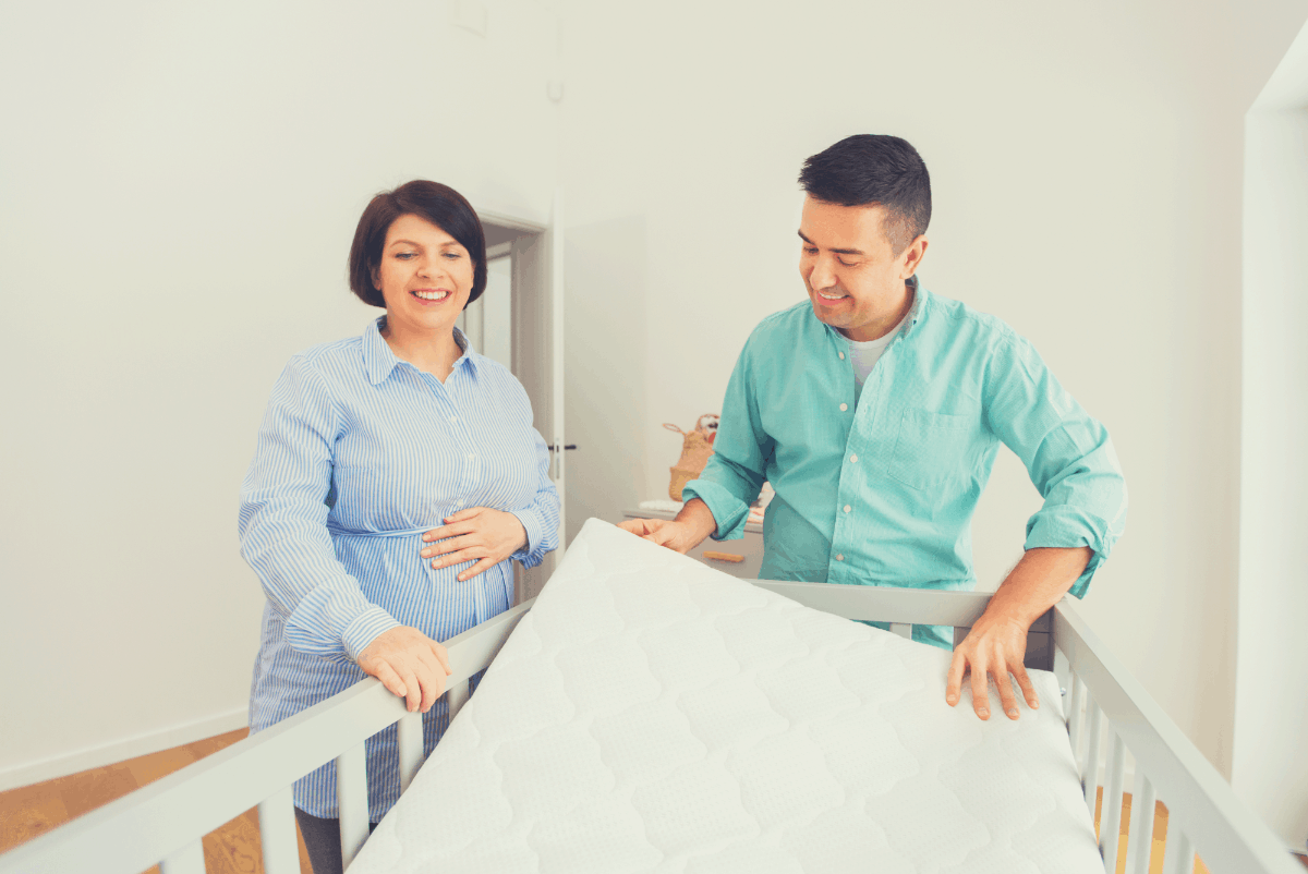 couple laying a crib mattress
