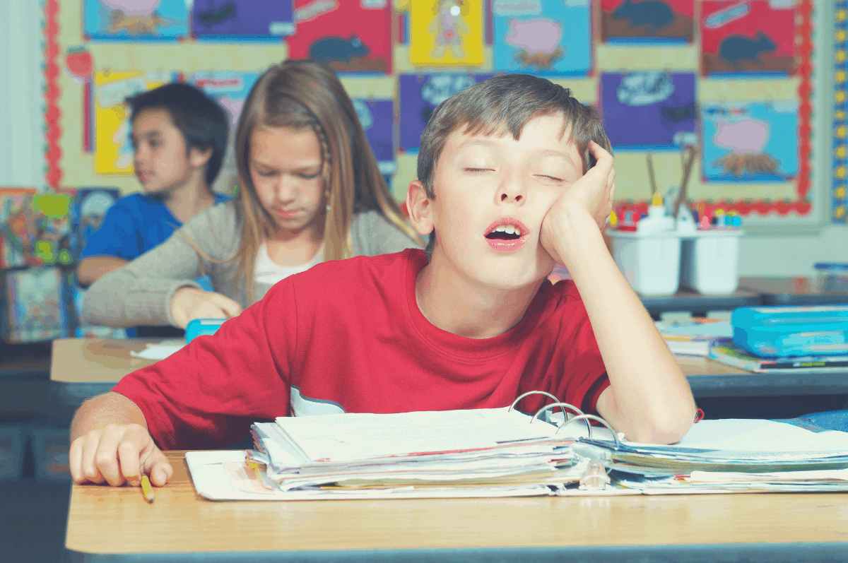 boy sleeping in class with an elbow propping the head