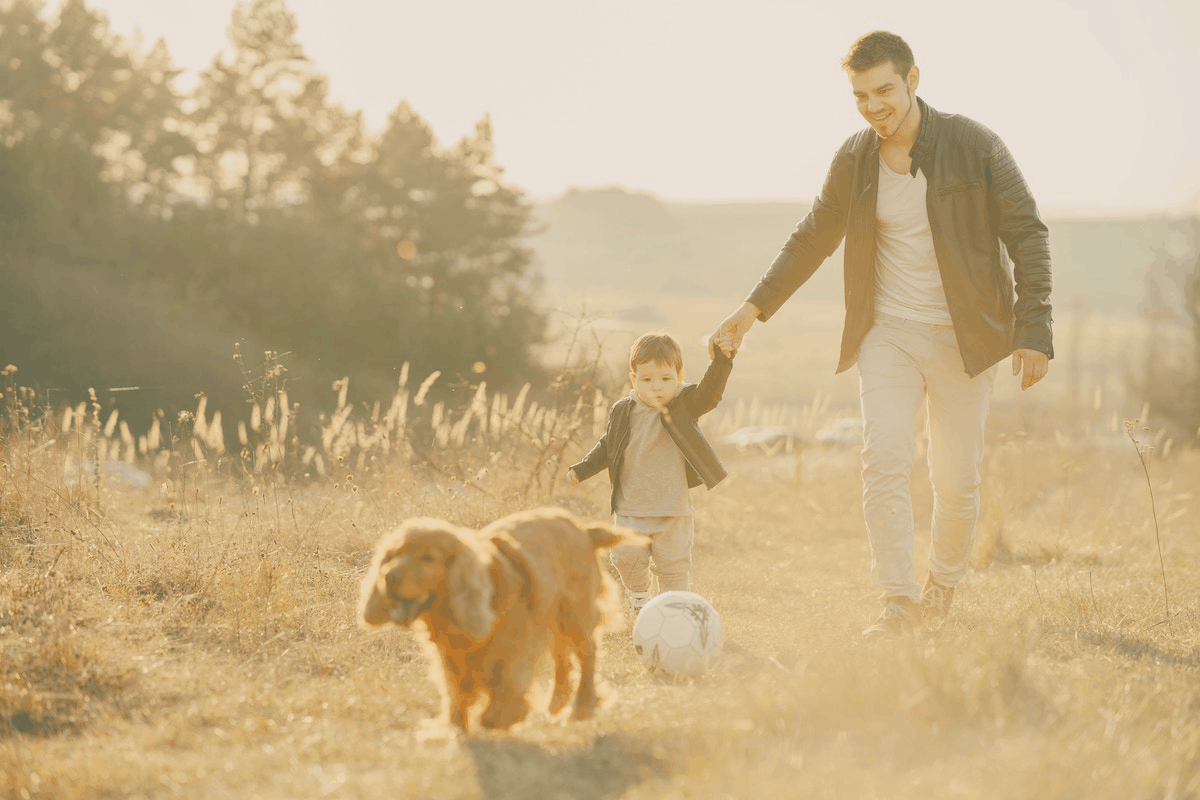 man and his son playing soccer outdoors with their dog