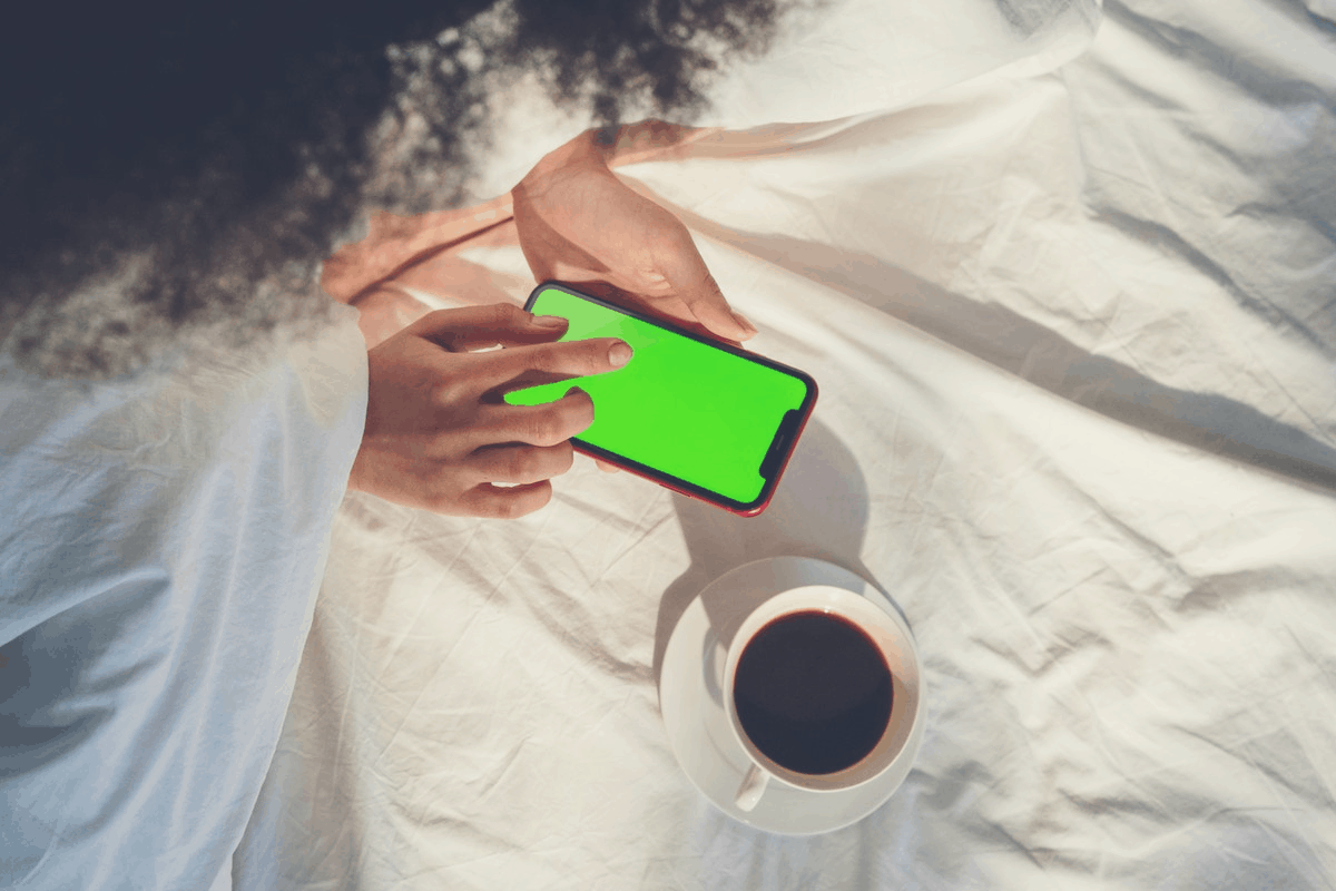 woman playing with a smartphone in bed