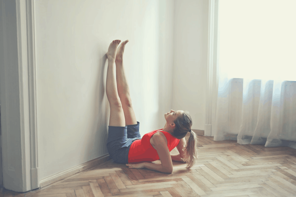 woman with raised legs up the wall