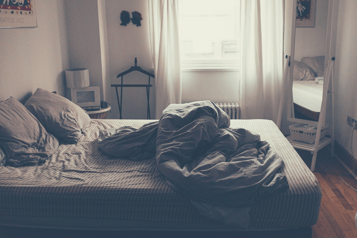 bed with dirty sheets and comforters