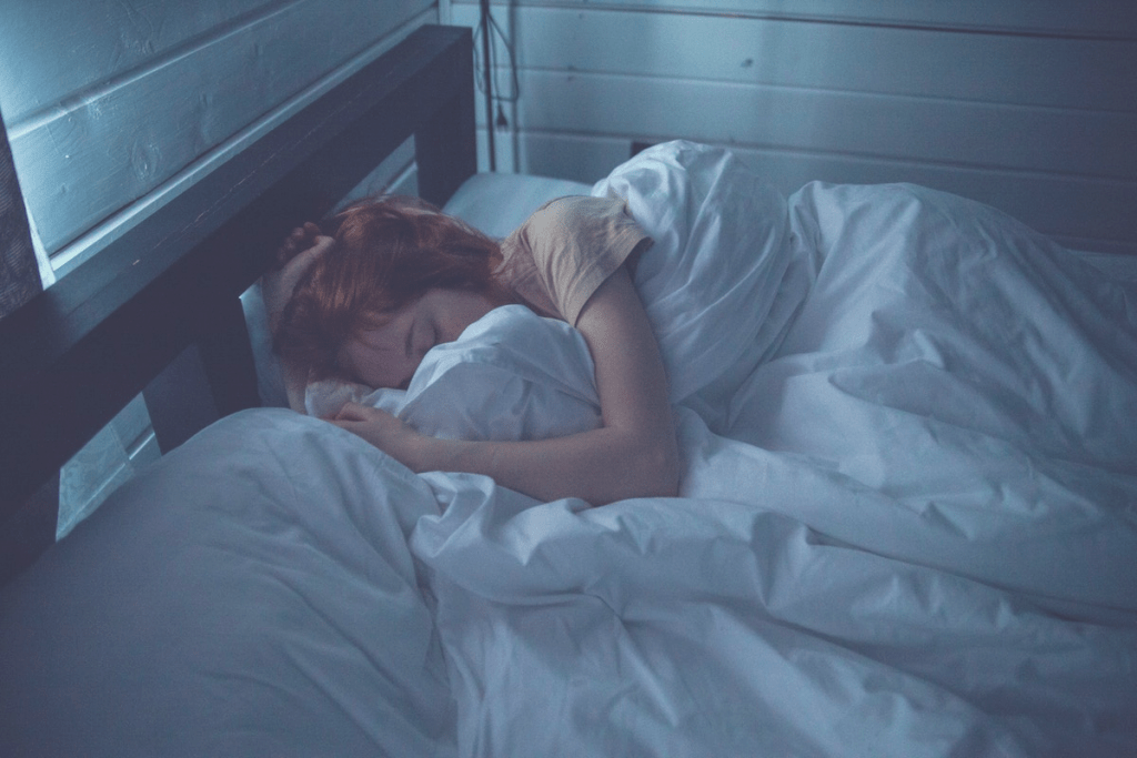 redhead sleeping in a bed with a pillow and white sheets