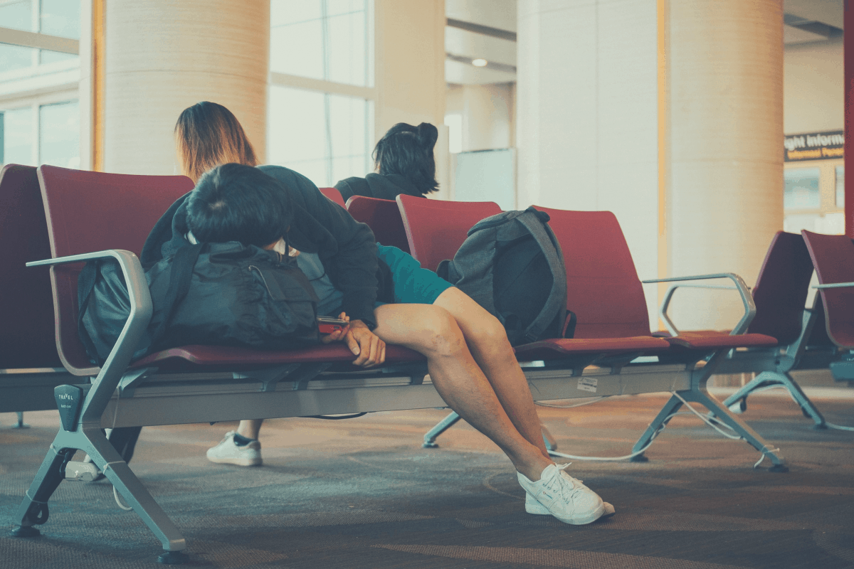 traveler sleeping in a sofa at the arrivals section of an airport