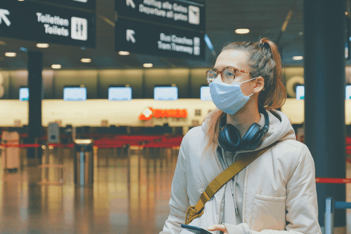woman in glasses with headphones and nose mask