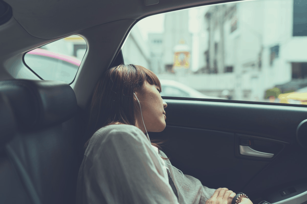 blonde woman sleeping in the backseat of a car