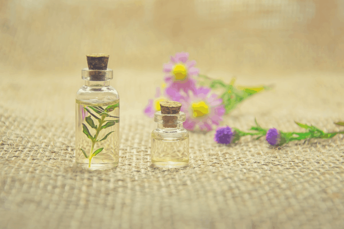 two clear bottles of essential oils and flowers