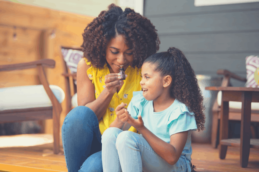 african american woman smelling an oil with her daughter
