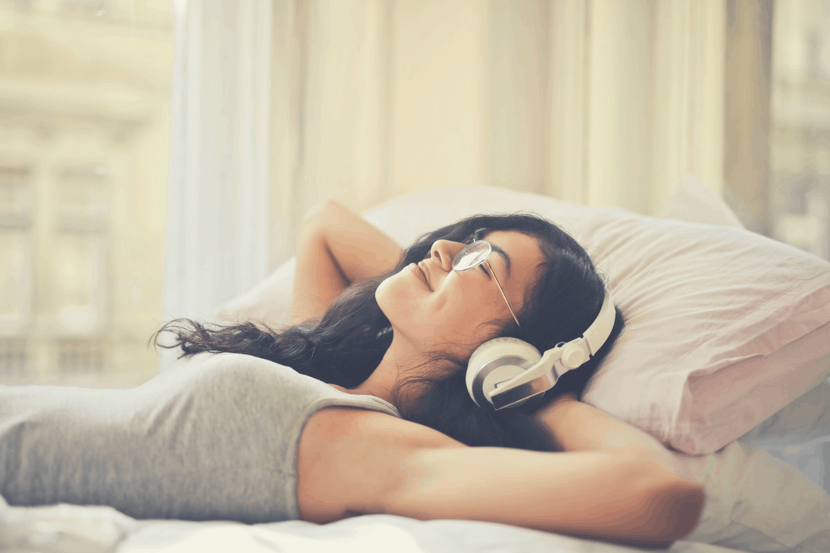 brunette in glasses listening to music in bed