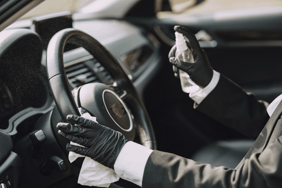 person in gloves and protective gear spraying the interiors of a car